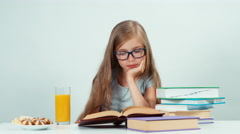 Close up portrait four-eyes 7-8 years reading book at the table isolated Stock Footage