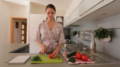 Young woman slicing a vegetable Stock Footage