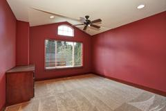 Red empty room with vaulted ceiling and beige carpet Stock Photos
