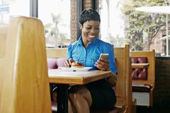 African American businesswoman using cell phone in restaurant Kuvituskuvat