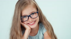 Close up portrait four-eyes schoolgirl reading book at the table Stock Footage