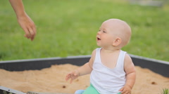 Cute baby boy playing with sand in a sandbox. Summer park and green grass in the - stock footage