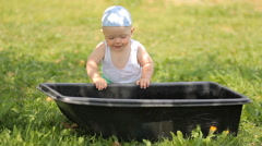 Adorable boy playing with a basin of water in the garden. He gets up and smiles - stock footage