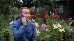 Young man calling on the phone near flowers in the garden. White, red and purple Stock Footage