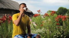 Adult man drinks morning coffee in garden, summer day. Against the background of Stock Footage