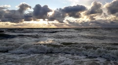 Sunset at Baltic Sea cloudy sky, small waves - stock footage