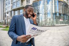 Joyful African man using telephone in city Stock Photos