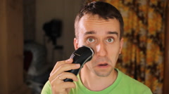 Hndsome young man shaving with electric razor. Electric shaver in living room Stock Footage