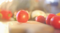 Female hands slicing red tomato with vegetables at background Stock Footage