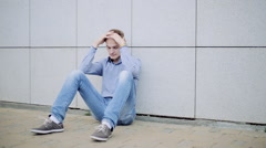 One depressed man sitting alone near wall Stock Footage
