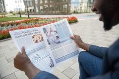 Happy businessman reads article from journal - stock photo