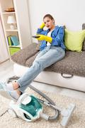 Tired woman watching television after vacuuming Stock Photos