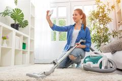 Woman with vacuum cleaner cleaning carpet and taking selfie Stock Photos