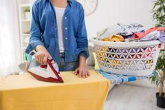 Woman ironing blouse on ironing board, close-up Stock Photos