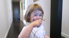 Baby painting her face looking at mirror Stock Footage