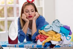 Lazy woman looks at laundry on ironing board Stock Photos