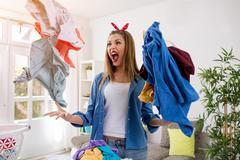 Aggressive frustrated woman throws laundry in the air Stock Photos