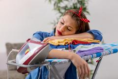 Worth tired young woman sleeping after ironing Stock Photos