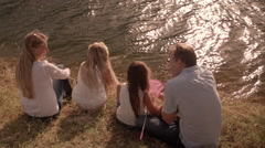 Family sitting by lake fishing with nets Stock Footage