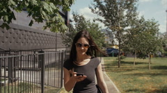 sexy business woman using smartphone walking near business building, steadicam - stock footage