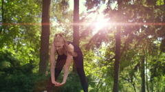 Woman training in good mood. Woman doing tilts forward. Sun flare in park Stock Footage