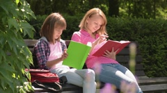 Mother and daughter reading books at park Stock Footage