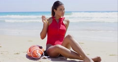 Pretty lifeguard sits on beach and twirls whistle Stock Footage