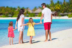 Happy family of four have fun together on white beach Stock Photos