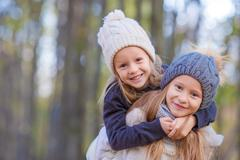 Little adorable girls at warm sunny autumn day outdoors - stock photo
