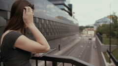sexy business woman using tablet standing on a bridge overlooking the road - stock footage