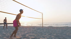 Volleyball player jumping to cath the ball on the beach during sunrise or sunset Stock Footage