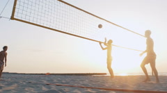 Group of people playing beach volleyball during sunrise or sunset Stock Footage