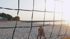 Two guys training to play beach volleyball during sunrise or sunset, slow motion Stock Footage
