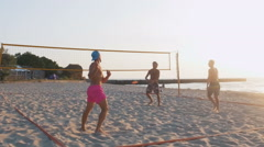 Group of people playing beach volleyball during sunrise or sunset, slow motion Stock Footage
