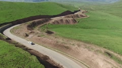 HIGH ANGLE AERIAL FOLLOW SHOT OF 4X4 DRIVING ON WINDY ROAD IN TIBET GRASSLANDS Stock Footage