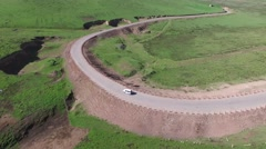 4K AERIAL FOLLOWING JEEP DRIVING ON WINDY ROAD IN THE SANGKE GRASSLANDS TIBET Stock Footage