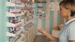 Attractive woman customer buying nail polish in makeup section. Girl in Stock Footage
