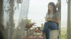 4K Young woman reading a book at beach house, enjoying the peace & tranquility Stock Footage