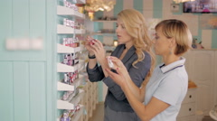 Young girls choosing new nail polish tone at cosmetic shop, best friends in Stock Footage