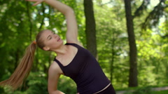 Fitness woman stretching outdoor. Fitness training in summer park - stock footage