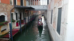 Romantic tour in gondola, rowed by a gondolier in the venice canal in Venice Stock Footage