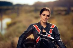 Female Motocross Racer Next to Her Motorcycle - stock photo