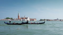 Pair gondolas rowed by a gondoliers through the San Marco Canal in Venice, Italy Stock Footage