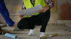 4K Portrait smiling architect looking at plans at construction site Stock Footage