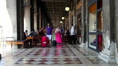 People walking through the hallway of Procuratie Nuove at San Marco Square Stock Footage