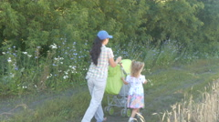 Little daughter and mother with a stroller walking along a path in a park. Stock Footage