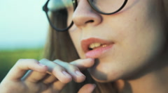 A young woman in glasses. Close-ups of the face, lips. Stylized as a movie. Blur Stock Footage