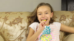 Girl licking candy on a stick in the form of lemon and raises the thumbs up Stock Footage