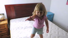 blonde baby jumping on mattress at home slow motion - stock footage
