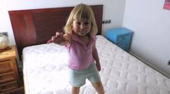 Blonde baby jumping on mattress at home Stock Footage